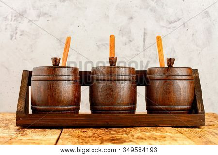 Wooden Decorative Barrels For Bulk Cereals With Wooden Measuring Spoons In Them, Lie In A Wooden Tra