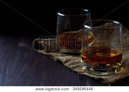 Alcoholic Drinks. Glass Of Whiskey With Ice On A Black Background. Two Glasses Of Whiskey On A Woode