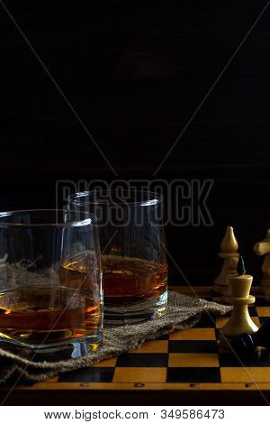 Alcoholic Drinks. Glass Of Whiskey With A Chess Queen And Pawn On A Black Background. Two Glasses Of