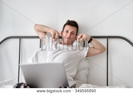 Smiling Handsome Young Man In A White Shirt And Pajama Sitting On A Bed With Laptop And Stretching.