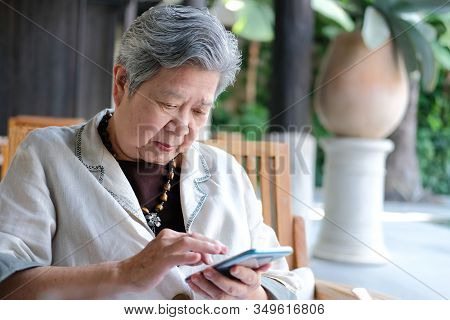 Elder Senior Woman Using Mobile Smart Phone. Elderly Female Holding Cellphone.