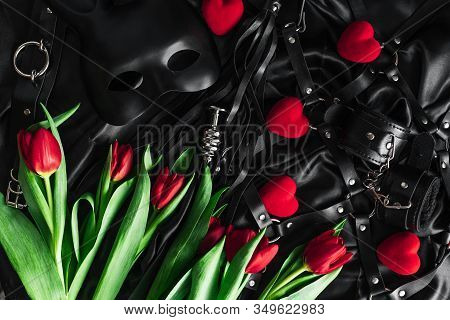 Explore The World Of Kinky Play. Top View Of Bdsm Leather Kit Against Of A Black Silk. Tulips