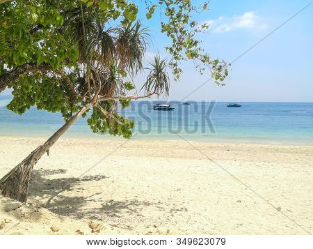 Exotic Island Beach Surrounded By Clear Blue Water, Empty Island In Thailand With Boats In The Dista