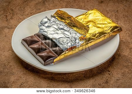 dark chocolate bar on plate being unwrapped, brown textured paper, dessert and temptation concept