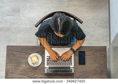 Asian Woman Freelancer Working On Laptop At Minimalism Coffeeshop