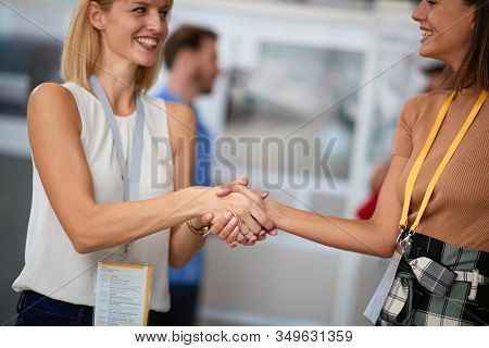 two young confident business female shacking hands watching at each other. business, done deal concept