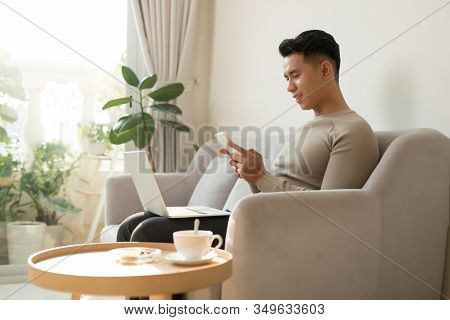 Young Asian Man Relaxing At Home On A Sofa With His Laptop Computer Chatting On His Mobile While Rea