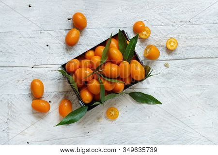 Kumquat Fruits In A Metal Box On A Grey Background Top View