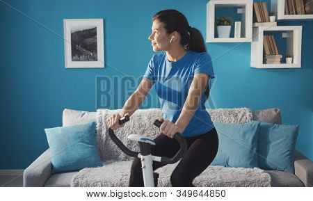 Sporty Happy Girl Training On Exercise Bike At Home Listening Music Looking Aside, Healthy Life
