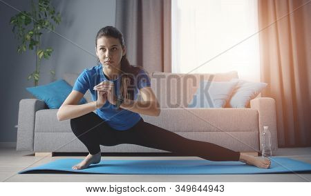Young Concentrated Woman Doing Side Lunge Yoga Position Training On Roll Mat On Floor At Home
