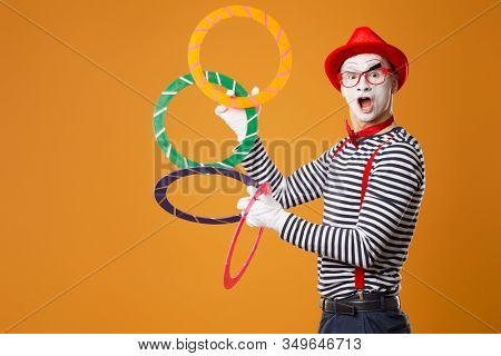 Mime man with multi-colored rings on orange background