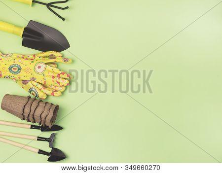 Garden Tools On Green Background Small Pots Yellow Garden Gloves Shovel Threads Rake Horizontal Top