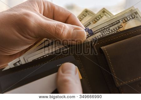 Brown Leather Wallet With Dollars In The Hands. Close Up.