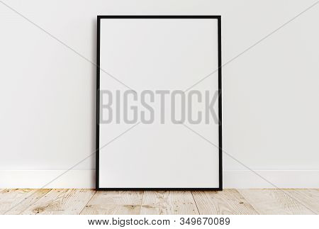 Empty Thin Black Frame On Light Wooden Floor With White Wall Behind It. Empty Poster Frame Mockup. E