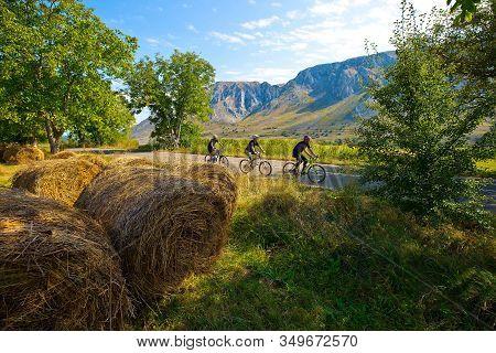 Cyclists Riding Through Mountain Landscape In Transylvania