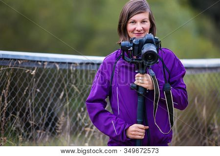 Brunette Woman Standing Near The Fence With A Camera