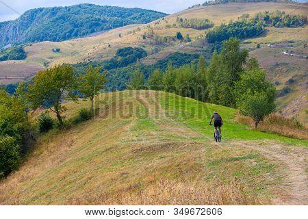 Biker Rides On Rural Road In Summer