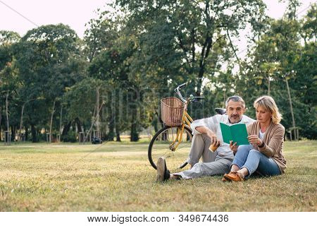 Caucasian Elderly Couple Relaxing And Sitting At The Park Reading The Book While Husband Looking To