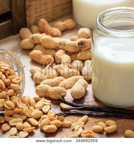 Peanut Milk On A Wood Table. Nuts And Glass With Milk, Non Dairy Milk For Vegans And Vegetarians