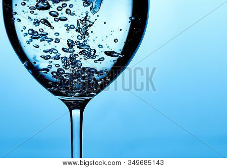 Pouring Water Into A Glass Against Light Blue Background