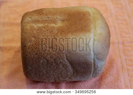 A Loaf Of Homemade Bread On An Orange Background