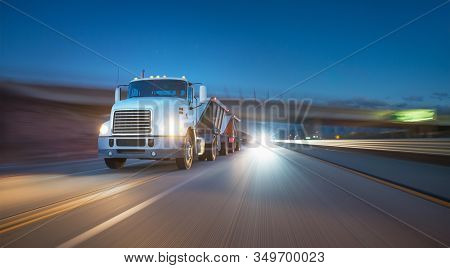 American style truck on freeway pulling load at night. Transportation theme. Road cars theme. Truckers heaven. Trailer passing the bridge