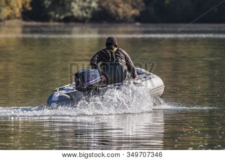 Man Sails On Inflatable Motorboat With Outboard Motor