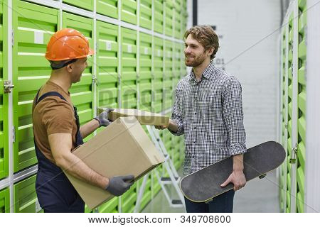 Young Worker In Work Helmet Giving A Parcel To Young Man While They Standing In Stockroom