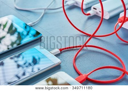 Two Mobile Phones And A Tablet Are On The Table, And All Devices Have Wires That Go To The Mobile Ch