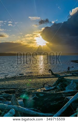 Sunbeams Pour Out From Behing Clouds Over The Puget Sound.