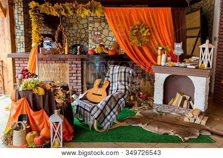 Autumn Rural Photozone. Composition With Pumpkins And Leaves Near Wall. Guitar, Orange Cloth And Pum
