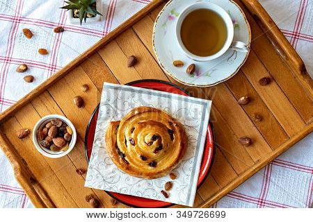 Pastry Rolls With Honey And Dry Grapes Served With Tea, Almond And Dry Grapes Aside Topview