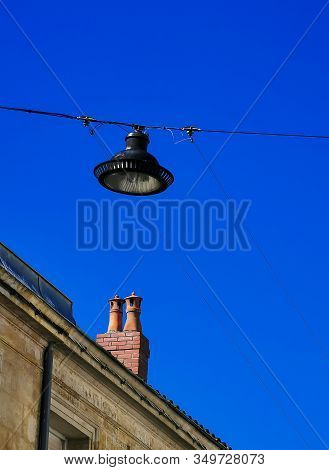 Partial View Of A House With Fireplace And Street Light Against Blue Sky.