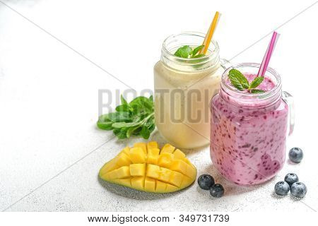 Delicious Blueberry And Mango Smoothie In Mason Jar On A Light Background. Healthy Food, Detox Diet.