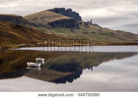 Two Boats With The Old Man Of Storr Reflecte On The Lake