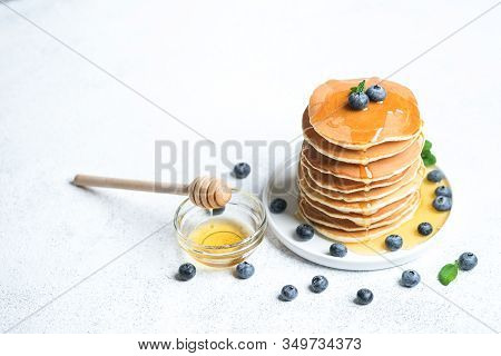 Pancakes With Berries And Honey On A Light Rustic Background Copy Space. Very Hearty Tasty Breakfast