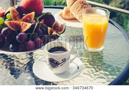Breakfast Table With Coffee, Orange Juice, Fruits And Croissants Outdoors In Sunny Summer Morning On