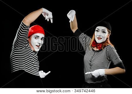 Mimes Points At Imaginary Object. Man And Woman Dressed In Striped Shirts