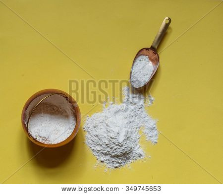 Floured Flour On A Yellow Background, A Copper Pot Of Flour And A Cooking Scoop, Horizontal