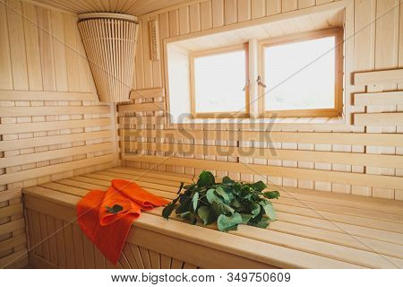 Light Sauna From Natural Wood With Accessories On Benches. Towel And Bath Brooms