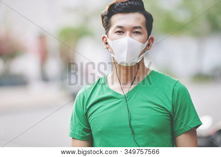 Serious Young Asian Man Lisening To Music In Headphones When Walking Outdoors In Protective Mask Dur