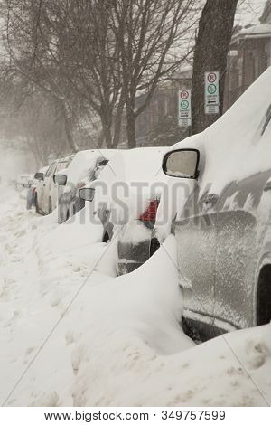 Car covered of snow and parked in a street during a snowstorm in Montreal in  Canada