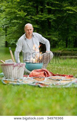 Mature man in casual wear with a flaming portable barbecue at an outdoor picnic