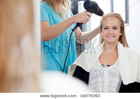 Mirror reflection of hairdresser drying long blond hair with blow dryer at parlor