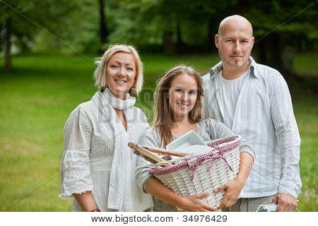 Portrait of a cute young female holding picnic basket while standing with parents
