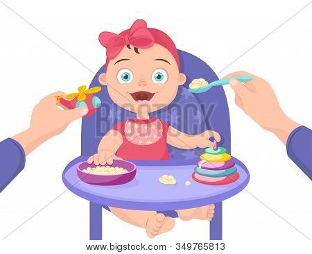 Mother Feeds The Child. Feeding Baby Porridge Sitting On A Chair. Feeding A Baby With A Spoon Distra