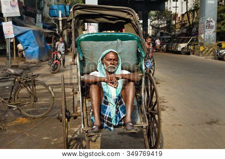 Kolkata, India - March 14, 2019: Indian Rickshaw Puller Sitting On His Rickshaw And Waiting For Pass