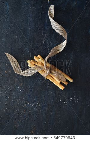 Bunch Of Grissini Breadsticks Tied Together With A Ribbon On Dark Background, Breadsticks Center Lay