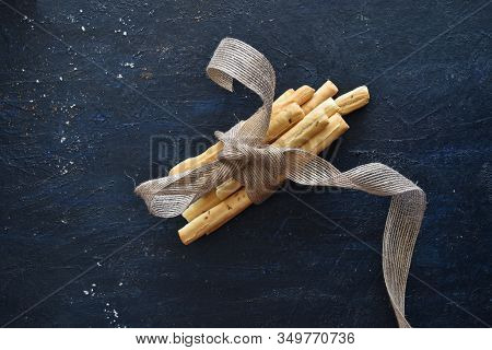Closeup Of Grissini Breadsticks Tied Together With A Ribbon On Dark Background, Breadsticks Top View