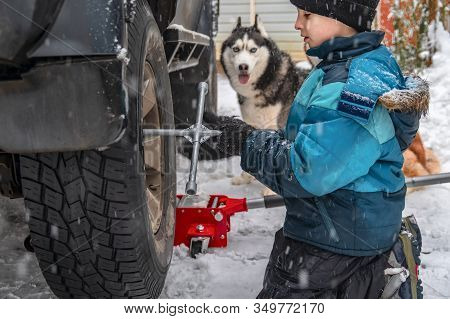 Boy Unscrews Nut On The Wheel Car. Replacing Wheels In Winter Day On The Background - House And Sibe